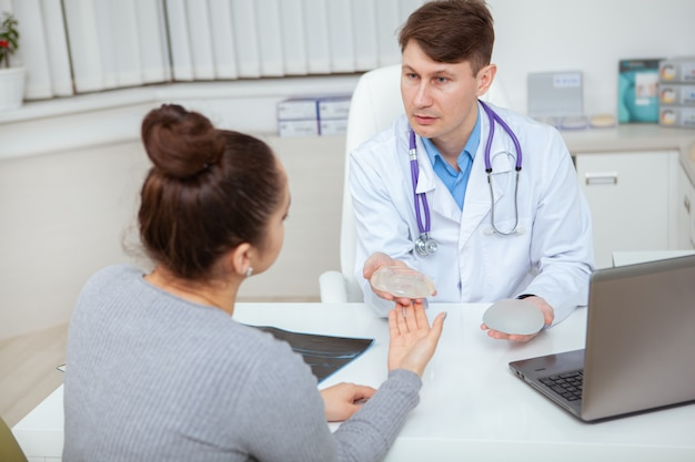 Professional plastic surgeon showing silicone breast implants to his female patient. Premium Photo