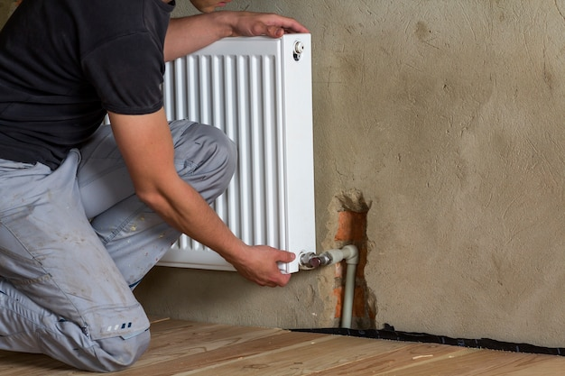 Professional plumber worker installing heating radiator on brick wall in an empty room of a newly built apartment or house. construction, maintenance and repair concept. Premium Photo