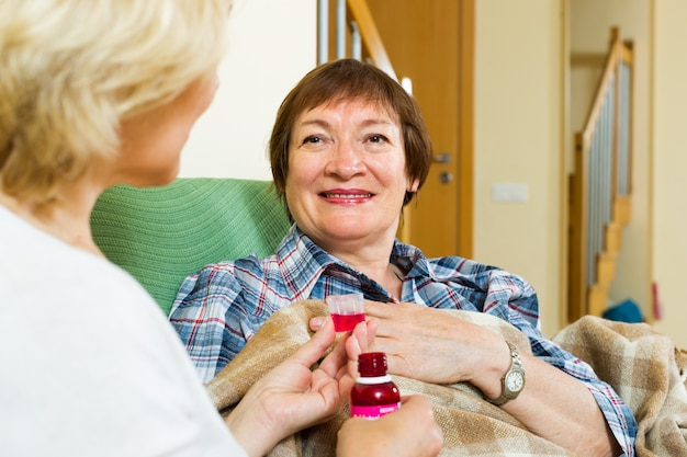 Professional retirement home employee offering  mixture to  patient Free Photo