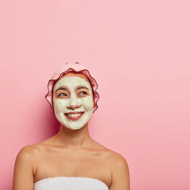 プロのスキンケアコンセプト。幸せな民族の女性は、肌のクレンジングと保湿のためにフェイシャルマスクを適用し、夢のような幸せな表情で見え、歯を見せる笑顔、柔らかいタオルに包まれ、屋内でポーズをとる 無料写真