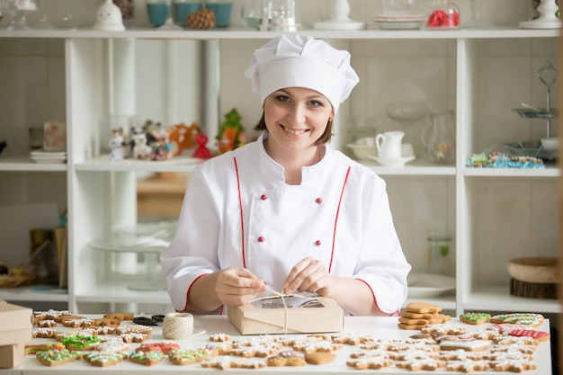 Professional smiling confectioner wrapping a box with cookies Free Photo
