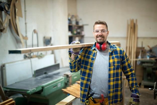 Falegname di mezza età sorridente professionista che tiene la plancia di legno nel laboratorio di falegnameria Foto Gratuite