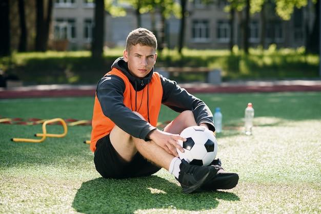 Профессиональный футбольный тренер в оранжевом жилете и свистке на шее. Premium Фотографии