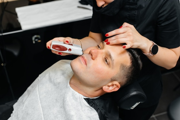 Professional stylist in a modern stylish barbershop shaves and cuts a young man's hair Premium Photo