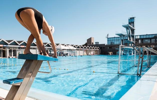 Nuotatore professionista pronto a tuffarsi in piscina Foto Gratuite
