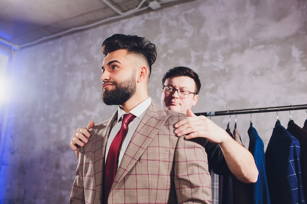 Professional tailor taking measurements for sewing suit at tailors shop Premium Photo