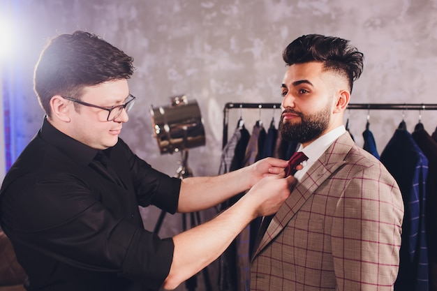 Professional tailor taking measurements for sewing suit at tailors shop Premium Photo