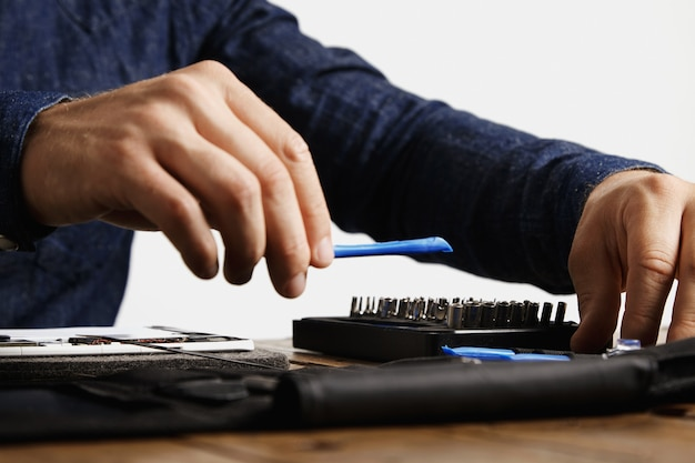 Professional takes speciall opening plastic instrument from his tool bag to repair tablet Free Photo