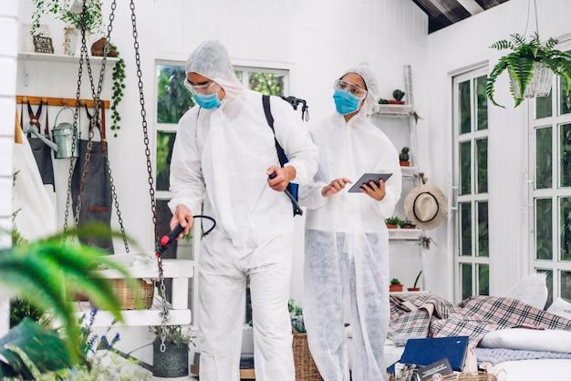 防護マスクと白いスーツ消毒剤スプレークリーニングウイルスの消毒作業員の専門チーム Premium写真