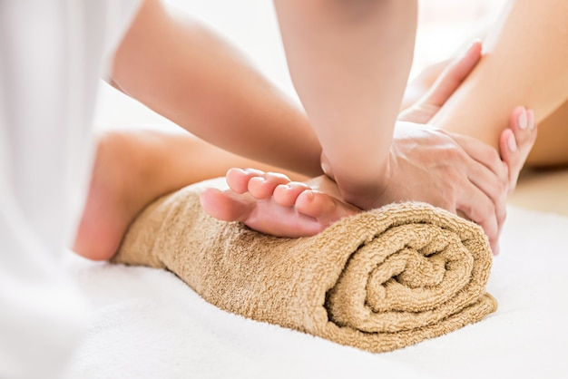 Professional therapist giving reflexology foot massage to a woman in spa Premium Photo