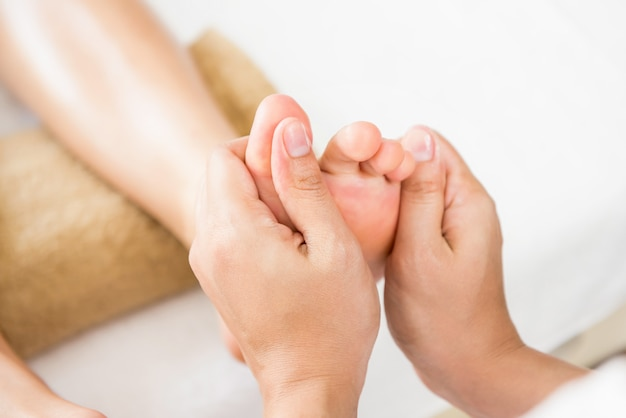Professional therapist giving reflexology thai foot massage to a woman in spa Premium Photo