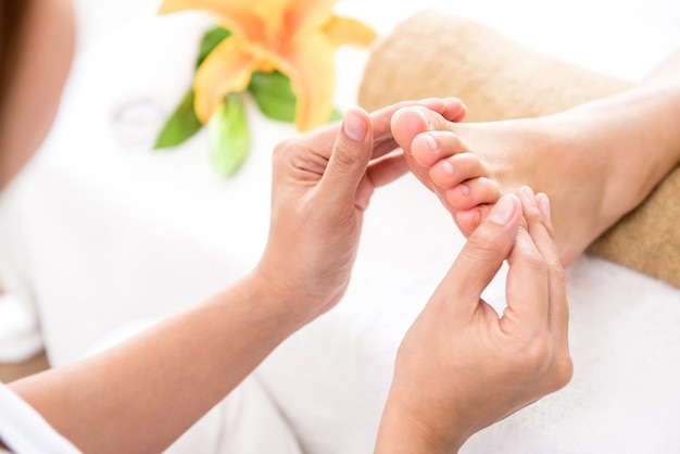 Professional therapist giving relaxing reflexology foot massage to a woman in spa Premium Photo
