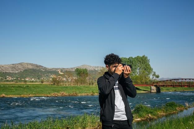 Professional traveler photographer taking photo of nature Free Photo