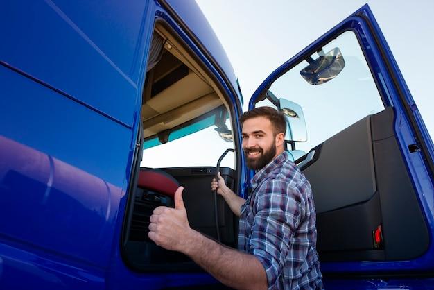 Профессиональный водитель грузовика садится в длинный грузовик и держит палец вверх Бесплатные Фотографии