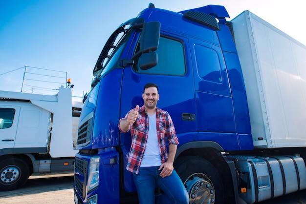 Профессиональный водитель грузовика перед длинным транспортным средством, подняв палец вверх, готовый к новой поездке Бесплатные Фотографии