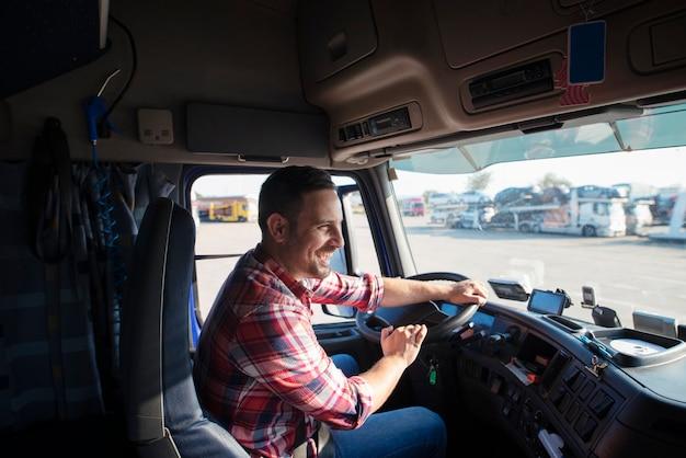 Профессиональный водитель грузовика с улыбкой за рулем грузовика и своевременной доставкой товаров Бесплатные Фотографии