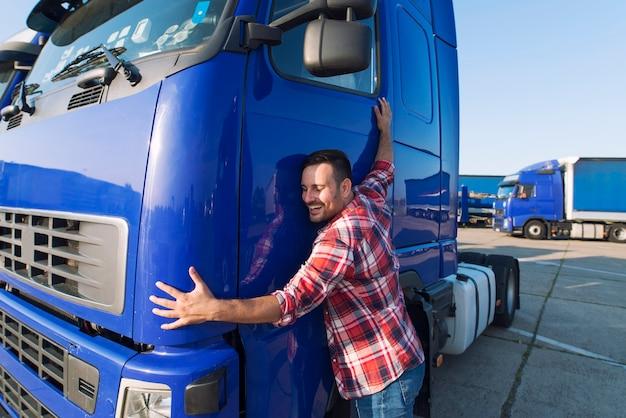 彼の仕事を愛する彼のトラックキャビンを抱き締めるプロのトラック運転手 無料写真