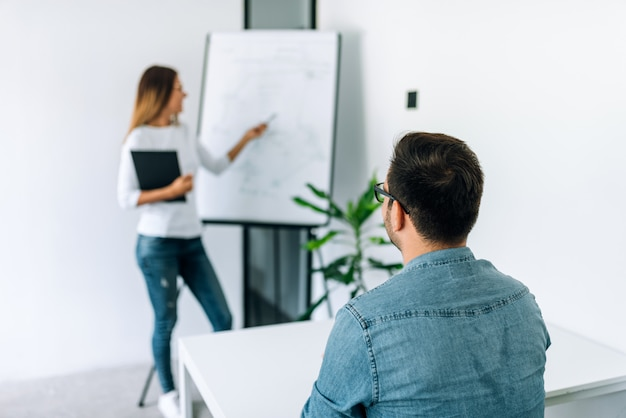 Professional tutor conducting private lesson on flipchart to a student. Premium Photo