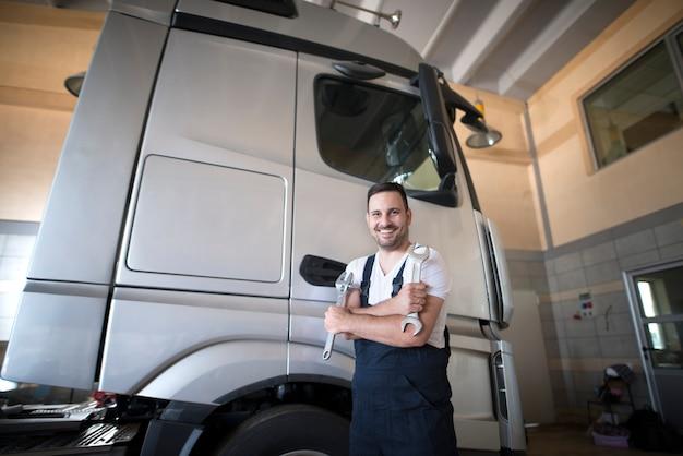 트럭 수리를 시작할 준비가 된 교차 팔과 렌치 도구로 워크샵에 서있는 전문 자동차 정비사 무료 사진
