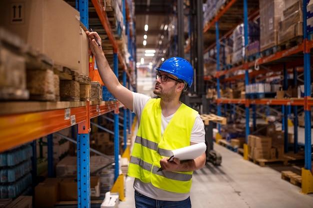 Профессиональный складской работник в защитной спецодежде держит контрольный список и проверяет инвентарь в складском помещении Бесплатные Фотографии