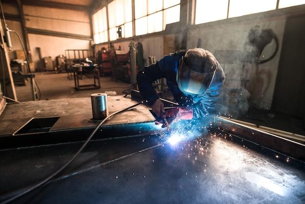 Professional welder welding metal construction parts in industrial workshop Free Photo