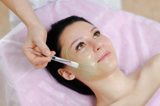 Professional woman applying green cream with a brush Free Photo