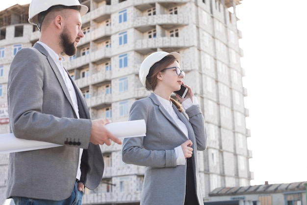 Professional woman architect talking on cellphone standing with her male colleague at construction site Free Photo