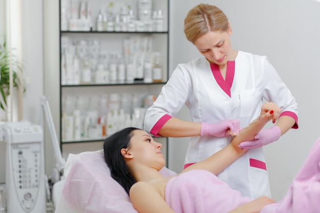 Professional woman making wax another woman in the arm Free Photo