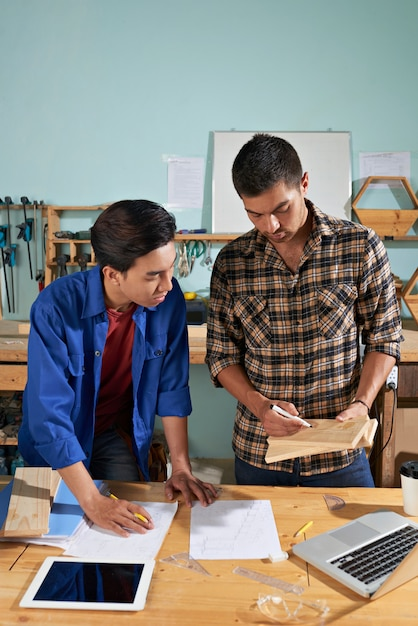 Professional worker explaining basics to his newcomer colleague Free Photo