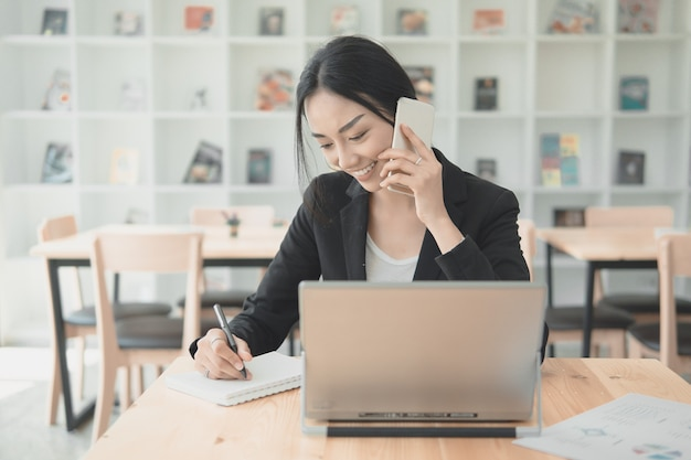 Professional working woman talking with mobile phone and writng document for listing information data. working in office with technology concept. Premium Photo