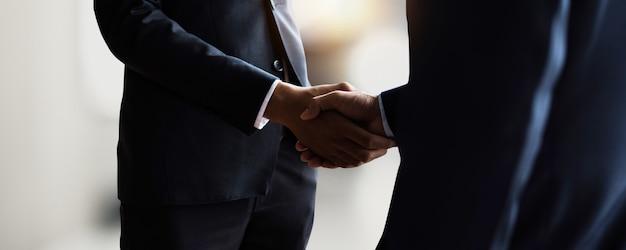 成功したコミュニケーション、交渉、経済的成功、および起業、最高のマーケティング、目標達成への企業祝賀の後に、パートナーとのプロの若手ビジネスハンドシェイク Premium写真