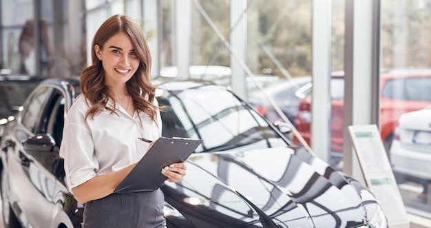 클립 보드 미소와 자동차 쇼룸에서 현대 자동차 근처에 서있는 동안 친절한 카메라를보고 전문 젊은 여성 딜러 프리미엄 사진