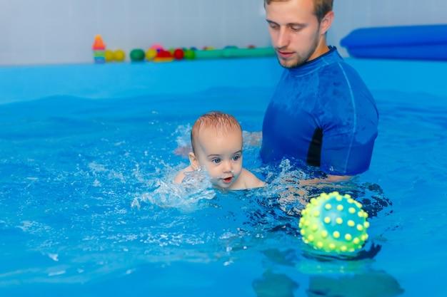 Профессиональный молодой пловец в синей кепке готов плавать в воде бассейна. Premium Фотографии