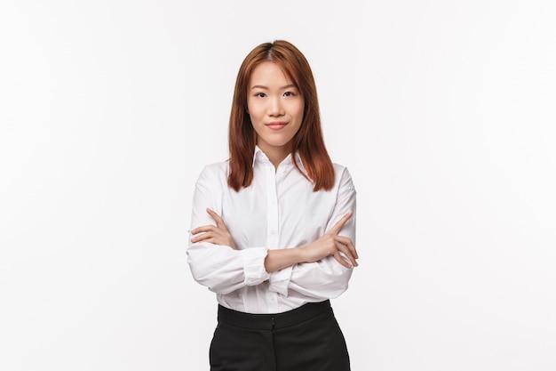 専門家、キャリア、ビジネスコンセプト。ホワイトカラーのシャツを着た深刻な格好の成功した女性起業家、クロスハンド胸の自信、笑顔とカメラの自信 Premium写真