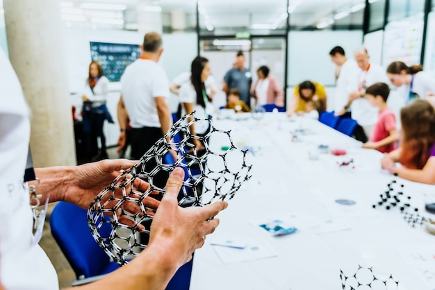 Professor holding in front of his students in biology class a molecular model of a graphene supermaterial. Premium Photo