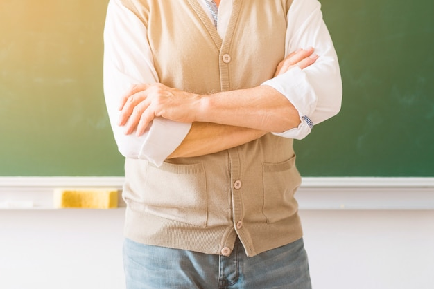 Professor with arms crossed standing against chalkboard Free Photo