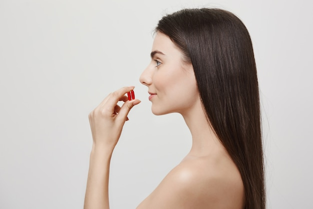 Profile of attractive naked woman taking vitamins Free Photo