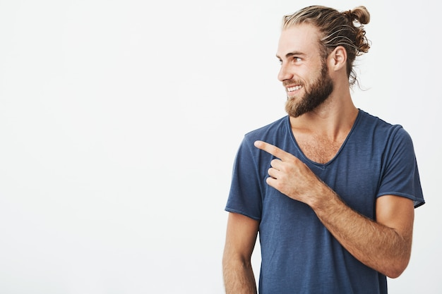 Profile of cheerful handsome man with fashionable hairstyle and beard smiling brightfully and pointing at copyspace Free Photo