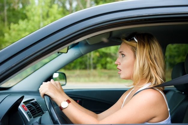 Profile face of fright woman sitting in the car and holds the wheel - outdoors Free Photo