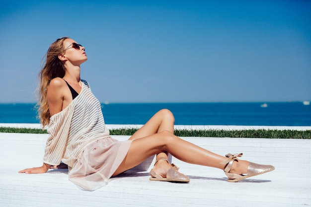 Profile of a gorgeous model in sunglasses, wearing stylish clothes, sitting on bench Free Photo