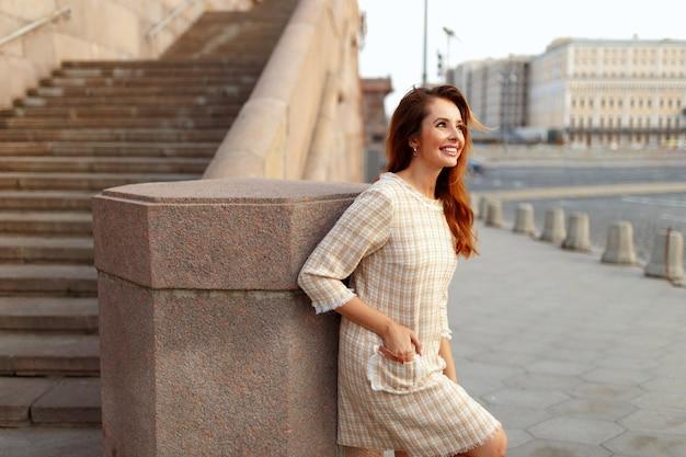 Профиль улыбающейся женщины с рыжими волосами, одетой в бежевое элегантное платье, позирующей снаружи, держа руки в кармане. Premium Фотографии