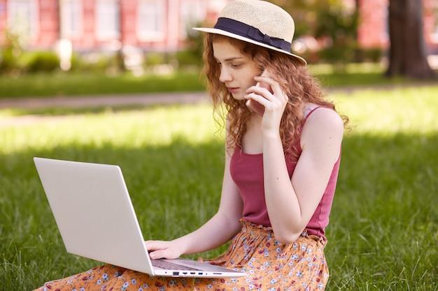 Профиль занятой задумчивой кудрявые волосы девушка работает в парке с ноутбуком, сидя на траве, в поисках информации, разговаривает по телефону, фокусируясь на ее домашних заданий. концепция студенческой жизни. Premium Фотографии