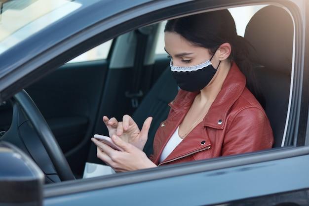 Профиль занят серьезных молодых женщин за рулем автомобиля, носить медицинскую маску для защиты, проведение мобильного телефона, использование устройства, чтение новостей, внимательно глядя на экран. Premium Фотографии