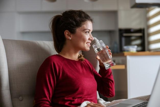 Профиль молодой брюнетки, сидящей дома и питьевой воды. Premium Фотографии