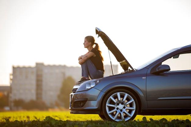 Профиль молодой стройной привлекательной женщины, сидящей на машине с выдвинутым капотом на зеленом лугу, ожидая помощи на фоне копией пространства ясного неба Premium Фотографии