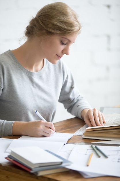 Profile portait of girl performing a written task in copybook ...