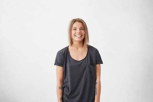 Profile portrait of beautiful young female with bobbed fair hair wearing casual grey t-shirt having tattoos on hands smiling pleasantly. trendy hipster woman having good mood while posing Free Photo