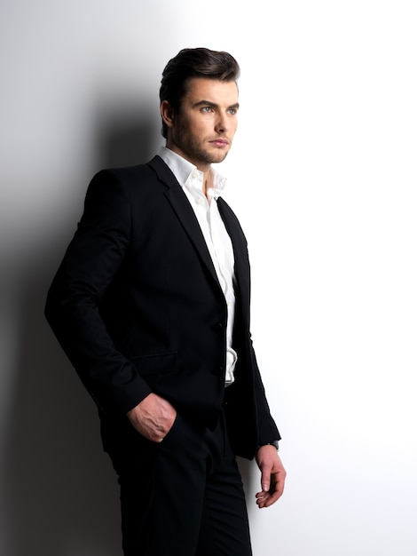 Profile portrait of a fashion young man in black suit posing at  studio Free Photo