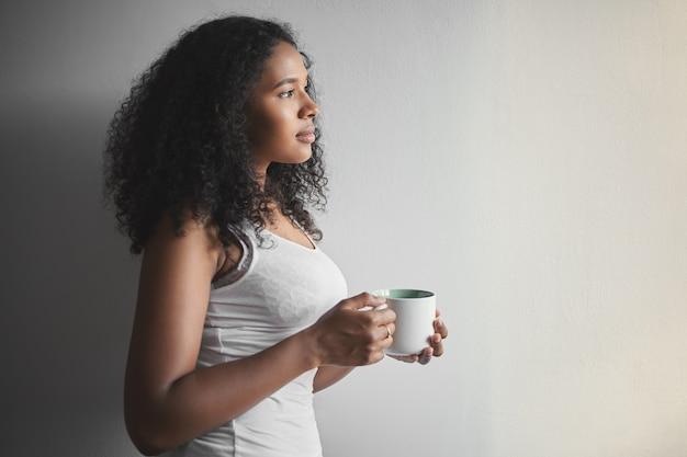 Ritratto di profilo di splendida attraente giovane donna di razza mista con acconciatura afro che tiene tazza, bere il caffè del mattino prima del lavoro, vestita in canottiera bianca persone, stile di vita, bevande e tempo libero Foto Gratuite