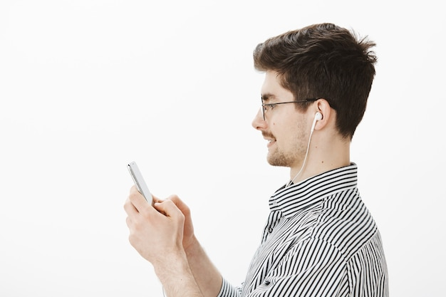 Profile portrait of joyful carefree attractive male model in glasses and striped shirt, holding smartphone while chatting with friends and listening music in earphones Free Photo